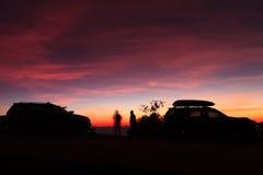 Puesta del sol púrpura viva espectacular y coche silueteados imagen de archivo libre de regalías