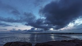 Puesta del sol pacífica con las luces del océano y de la ciudad del rompeolas almacen de metraje de vídeo