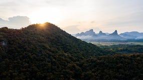 Puesta del sol del paisaje de la visión aérea en el campo de las montañas Fotografía de archivo