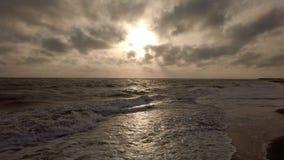 Puesta del sol panorámica de la hora de oro que sorprende en el mar con el cielo dramático y la luz hermosa entre las nubes almacen de metraje de vídeo