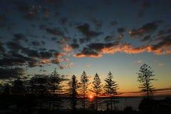 Puesta del sol perfecta sobre la montaña a través del océano Imagenes de archivo