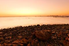 Puesta del sol, piedras y línea de la playa Foto de archivo libre de regalías