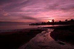 Puesta del sol, playa y embarcaderos del océano Imágenes de archivo libres de regalías