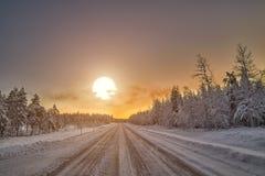 Puesta del sol polar de la noche sobre el camino en Finlandia Imágenes de archivo libres de regalías