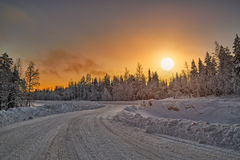 Puesta del sol polar de la noche sobre el camino en Finlandia Foto de archivo libre de regalías