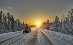 Puesta del sol polar de la noche sobre el camino en Finlandia Foto de archivo