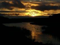 Puesta del sol por el agua Fotografía de archivo libre de regalías