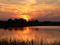 Puesta del sol por el lago Fotografía de archivo libre de regalías