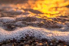 Puesta del sol por el resplandor de oro del mar Imagen de archivo libre de regalías