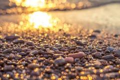 Puesta del sol por el resplandor de oro del mar Imagen de archivo