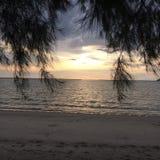 Puesta del sol por la playa con la nube dramática Foto de archivo