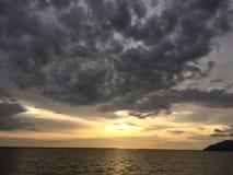 Puesta del sol por la playa con la nube dramática Foto de archivo libre de regalías