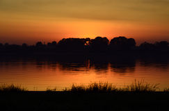 Puesta del sol por un lago Foto de archivo
