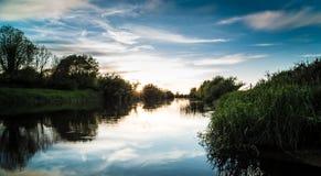 Puesta del sol por un río tranquilo hermoso Foto de archivo