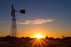 Puesta del sol preciosa en Kalahari con el molino de viento y la hierba Imagenes de archivo