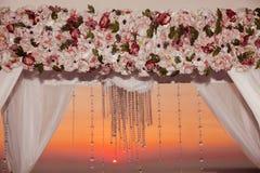 Puesta del sol Primer de la decoración del arco de la ceremonia de boda con el arrangem de la flor Fotografía de archivo libre de regalías