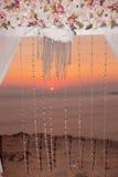 Puesta del sol Primer del arco de la ceremonia de boda con el centro de flores Fotografía de archivo