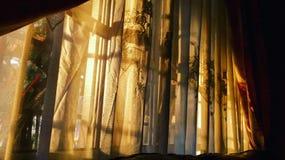 Puesta del sol que brilla a través de las cortinas Imagenes de archivo