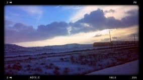 Puesta del sol que compite con del tren Imagenes de archivo