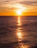 Puesta del sol que echa punto culminante largo sobre el mar Imágenes de archivo libres de regalías