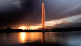 Puesta del sol que golpea agua del jet la D famosa 'en Ginebra, Suiza imagenes de archivo