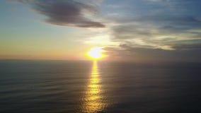 Puesta del sol que pasa por alto el océano y un barco flotante Rayos de Sun en el agua Sol rojo y un barco solo almacen de video