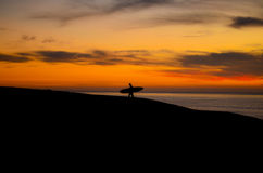 Puesta del sol que practica surf Imágenes de archivo libres de regalías