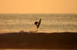 Puesta del sol que practica surf Foto de archivo libre de regalías