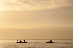 Puesta del sol que practica surf de la canoa Foto de archivo libre de regalías