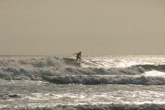 Puesta del sol que practica surf en la playa del kuta. Foto de archivo