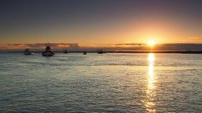 Puesta del sol que refleja en el mar con los pequeños barcos de pesca anclados en el agua tranquila, Orford, Suffolk imagen de archivo