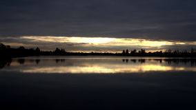 Puesta del sol que refleja en un lago Imagen de archivo