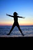 Puesta del sol que salta en la playa del mar Imagen de archivo