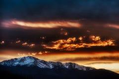 Puesta del sol que sorprende que es Pikes Peak y las nubes hermosas del contraste de las montañas rocosas foto de archivo