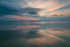 Puesta del sol reflejada en agua en la playa Imágenes de archivo libres de regalías