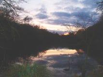 Puesta del sol reflejada en el lago imagenes de archivo