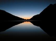 Puesta del sol reflejada en el lago inmóvil Imagen de archivo libre de regalías