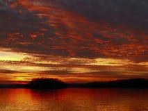 Puesta del sol roja dramática en el lago Foto de archivo