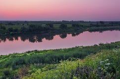 Puesta del sol roja en el río Foto de archivo