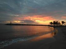 Puesta del sol roja en la playa Aquadillia Puerto Rico los E.E.U.U. de Rompeolas imagenes de archivo