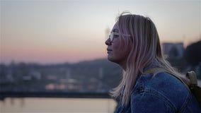 Puesta del sol roja hermosa sobre el río La muchacha se sienta en la costa y las miradas en la distancia Marco cinem?tico hermoso metrajes