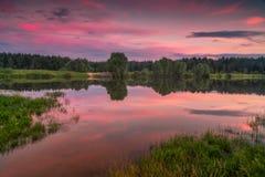 Puesta del sol roja por el lago con la reflexión Imagen de archivo libre de regalías