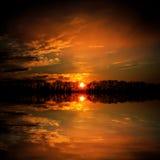 Puesta del sol roja sobre el agua del lago Imagen de archivo libre de regalías