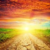 Puesta del sol roja sobre el camino de la sequía Foto de archivo libre de regalías