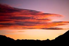 Puesta del sol roja sobre silueta de las montañas Imagen de archivo libre de regalías