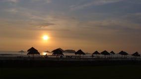 Puesta del sol roja y paraguas 97 kilómetros al sur de Lima, Perú Imagenes de archivo