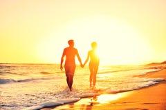 Puesta del sol romántica de las manos de los pares de la playa del verano que se sostiene Fotografía de archivo