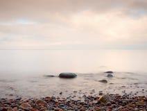 Puesta del sol romántica en el horizonte, reflejando en orilla, mar liso de la tarde, concepto del viaje Imagenes de archivo