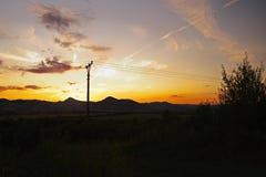 Puesta del sol romántica en el stredohori de Ceske de la región en paisaje checo con los campos, los pilones y las montañas Miles Imagen de archivo libre de regalías