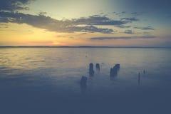 Puesta del sol romántica sobre el océano con las nubes Imagen de archivo libre de regalías